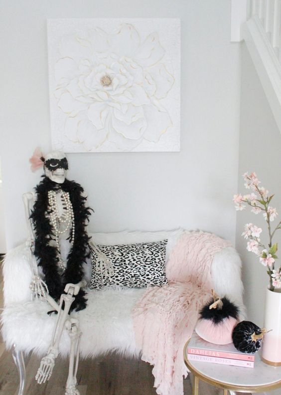 a glam nook with a skeleton dressed in jewelry and a fur scarf, with black and pink pumpkins is a romantic and cute idea