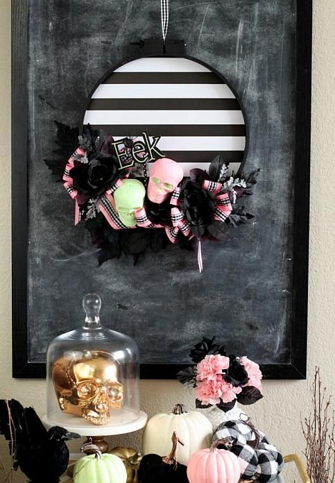 a gorgeous and non-typical striped Halloween wreath with neon skulls, black and pink bows is a cool idea with a slight vintage feel