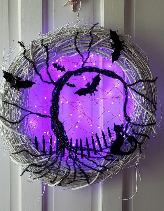 a gorgeous glowing Halloween wreath of whitewashed vine, black bats and cats, a black bottle cleaner tree and purple lights is breathtaking