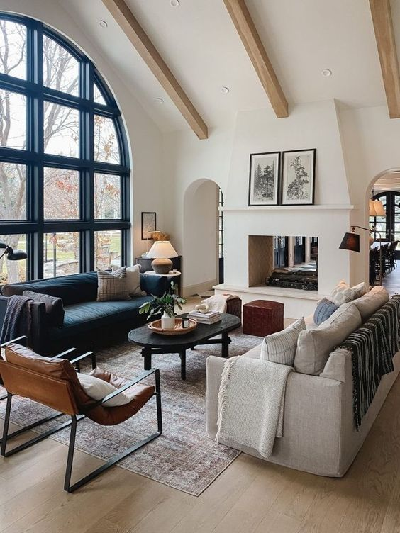 a gorgeous living room with an arched window, wooden beams, a double-sided fireplace, a black and a neutral sofa, a black coffee table and leather chairs
