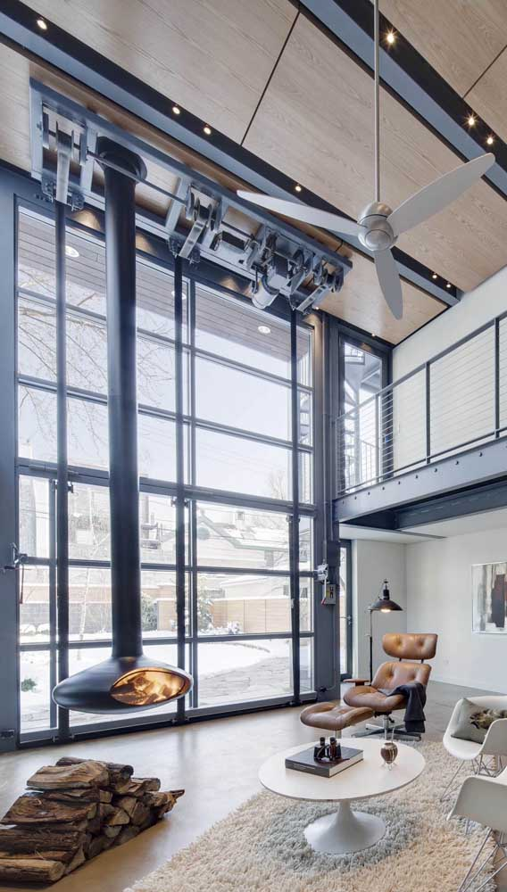 a gorgeous modern liivng room with a double-height ceiling and a garage door that can open up the space to the garden is amazing