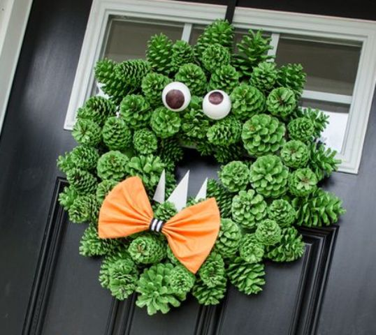 a green pinecone monster Halloween wreath with googly eyes, an orange bow and some teeth is a very cool idea for styling your front door