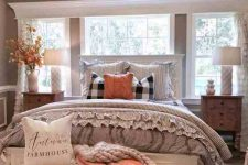 a greige farmhouse bedroom with a white bed, a white upholstered bench, stained nightstands, an orange pillow, an orange plaid blanket and fall leaves
