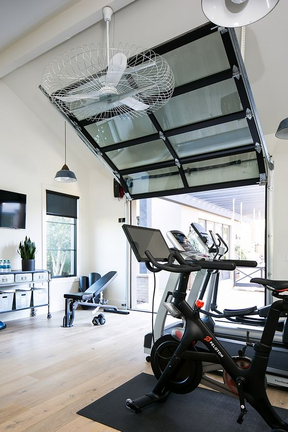 a home gym with a smoked glass garage door that opens it up to the backyard to get fresh air in the space, it's important while doing exercises