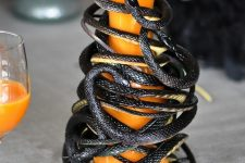 a jug with juice completely wrapped with black snakes is a stylish and scary solution for Halloween
