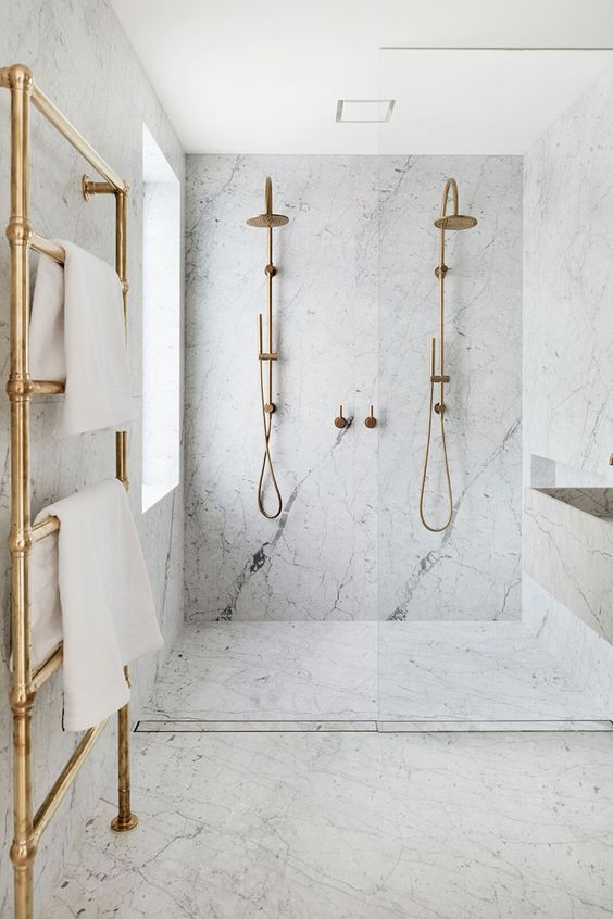 a laconic and luxurious white bathroom fully clad with stone, with a large shower space, brass fixtures and a radiator is a gorgeous idea