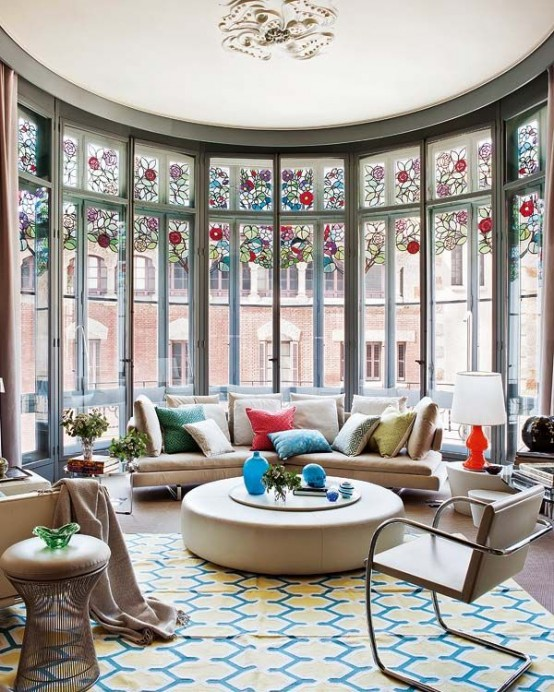 a large and bright living room with a rounded window with stained glass, neutral modern furniture and colorful textiles is welcoming
