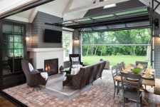 a large garage door is perfect to connect a living room with a desk to create an ultimate entertainment space