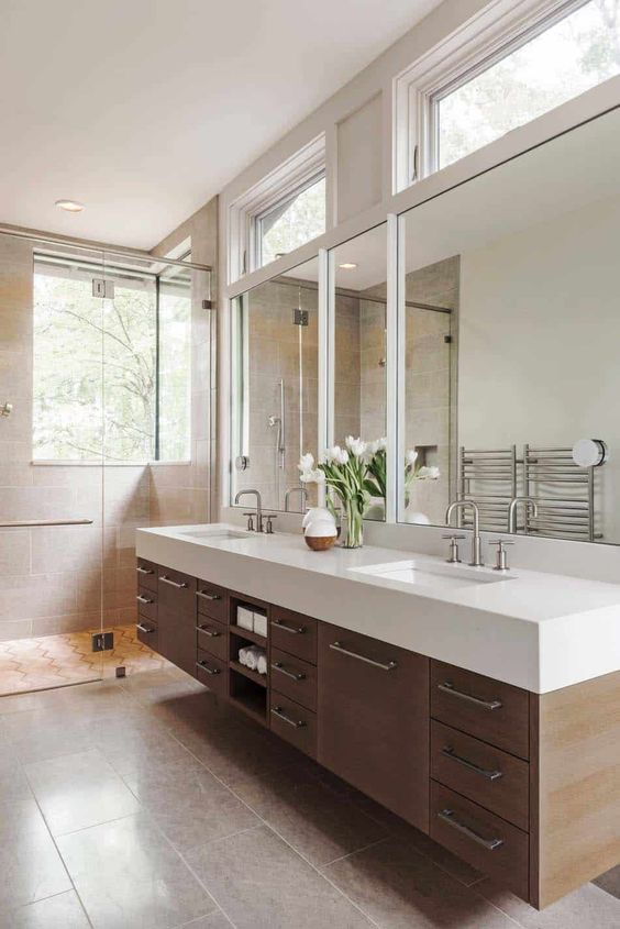 a large modern farmhouse bathroom with a window, a large floating vanity with a stone countertop, clerestory windows for more light
