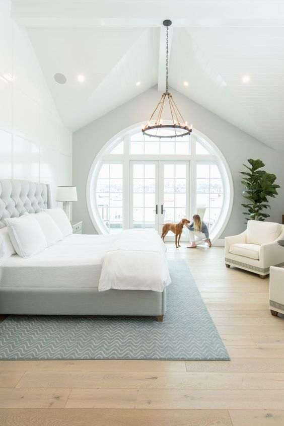 a large modern farmhouse bedroom with paneling, a grey bed with neutral bedding, creamy chairs, a chandelier and a porthole window that includes a door