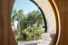 a large round window with a daybed placed right on the round windowsill and with a view of the palms outdoors