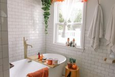 a lively fall bathroom with a tree stump side table with a faux pumpkin, an orange towel, green and orange garlands and cute pumpkins and bold mugs is amazing