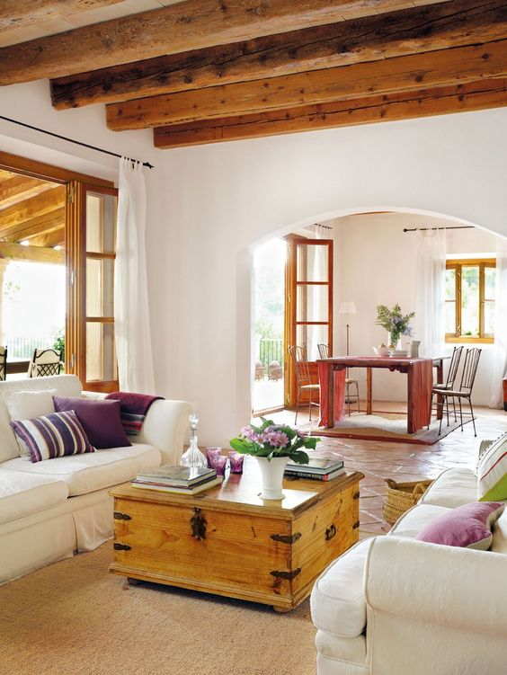 a living room with wooden beams, neutral seating furniture, a wooden coffee table and bright pillows and blooms
