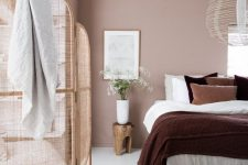 a lovely attic bedroom with a dusty pink accent wall, a neutral bed with bold bedding, a pendant lamp, rattan space divider is very cool