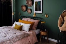 a lovely boho bedroom with a dark green accent wall, a metal bed with pink bedding, a gallery wall of decorative baskets and an artwork