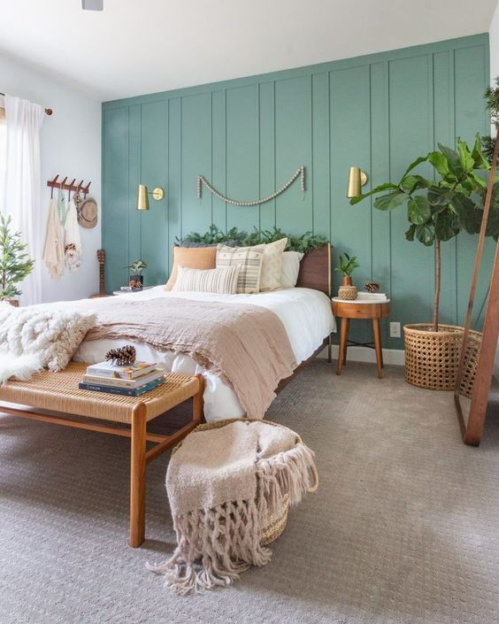 a lovely boho bedroom with a green paneled wall, a plywood bed, a woven bench, round plywood nightstands, potted plants and gilded touches