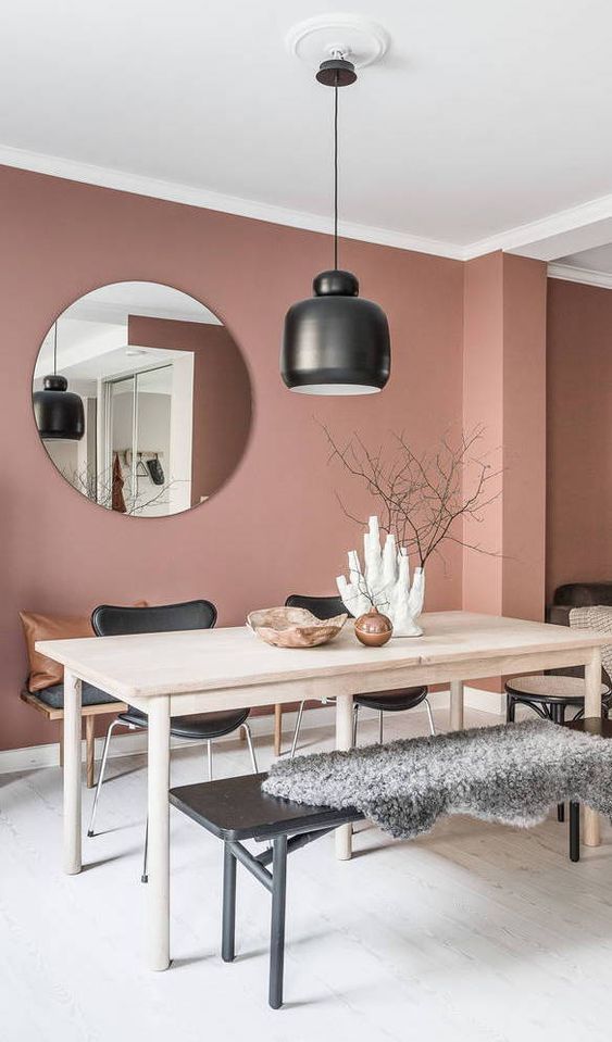 a lovely dining space with a dusty pink accent wall, a wooden table, black chairs and a bench, a pendant lamp and a round mirror is cool