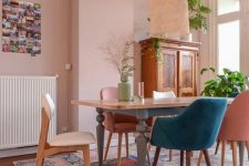 a lovely eclectic dining room with a blush accent wall, a vintage dining table, mismatching chairs, potted plants, a woven pendant lamp