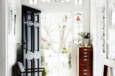a lovely entryway with stained glass sidelights and a black door, a vintage bench, a fire cabinet and a dark chair with navy upholstery