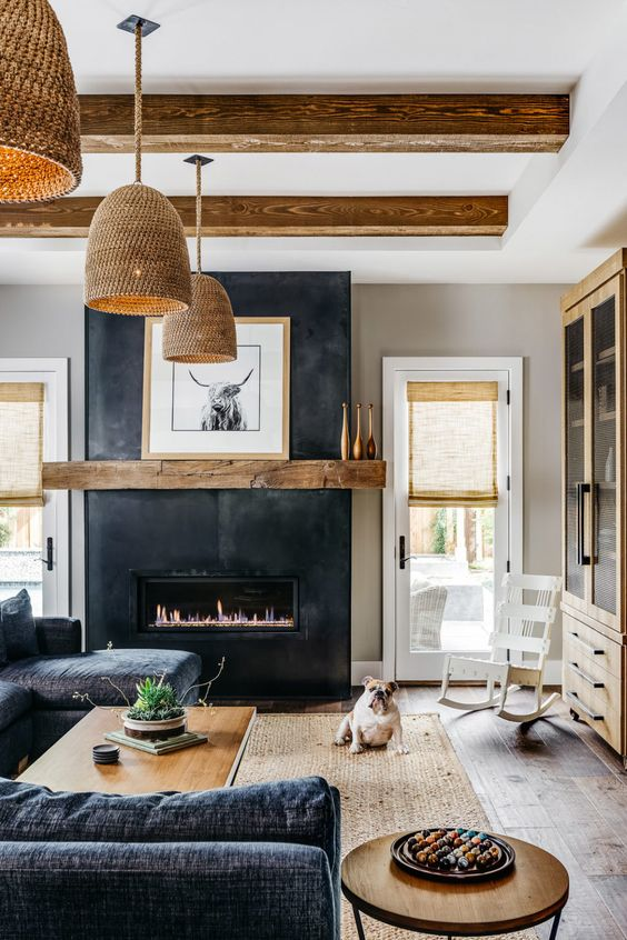 a lovely farmhouse living room with light-stained wooden beams, a fireplace in black, a black sectional, plywood side tables and woven pendant lamps