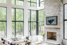 a lovely light-filled farmhouse living room with wooden beams, a fireplace clad with stone, neutral seating furniture, coffee tables and double-height windows