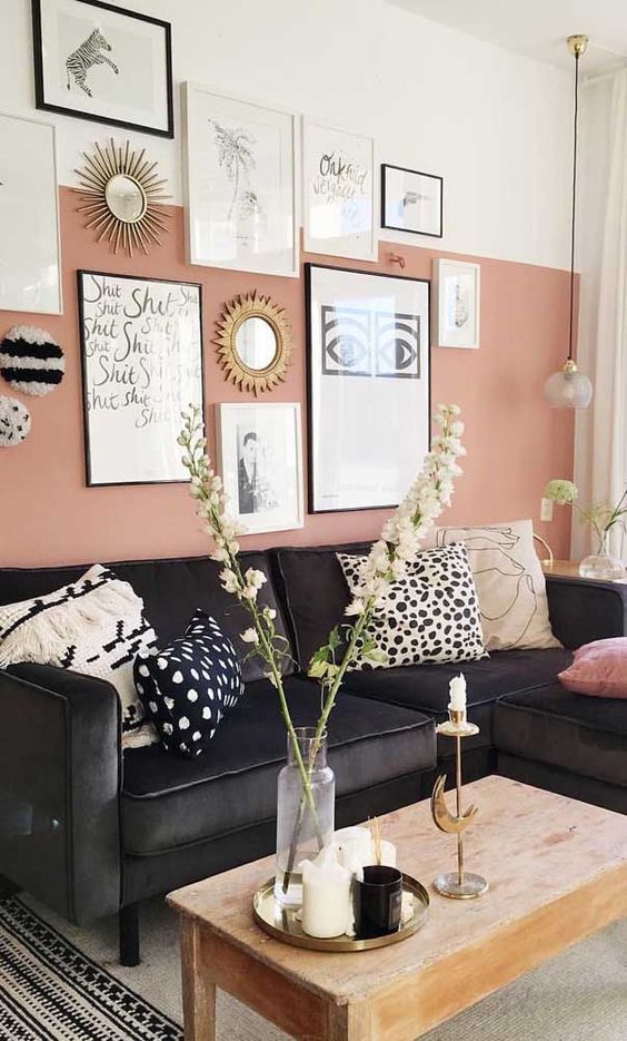 a lovely living room with a color block pink and white wall, a gallery wall, a black sectional, a coffee table and pendant lamps