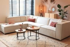 a lovely living room with a pink and white color block wall, a white sectional, a duo of coffee tables, potted plants and a mirror in a wooden frame