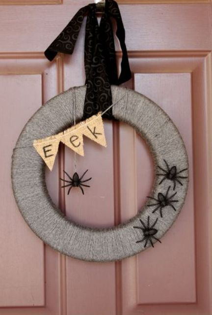 a lovely rustic Halloween wreath wrapped with yarn, with black spiders, a burlap bunting and chic ribbon is amazing