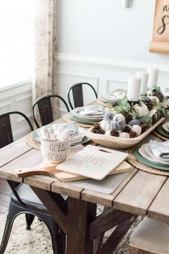 a lovely rustic Thanksgiving tablescape with an uncovered table, pinecones, pumpkins and green plates is simple and cool
