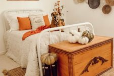 a lovely rustic fall bedroomw ith a white forged bed, a wooden chest that doubles as a bench, faux and fabric pumpkins, decorative baskets and fall leaves