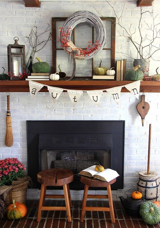 a lovely rustic fall mantel with bold pumpkins, a wreath with berries, a candle lantern, branches in planters and books is all cool