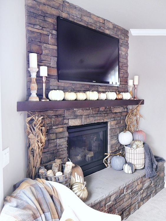 a lovely rustic fall mantel with lots of faux pumpkins, corn husks, pillar candles, a basket with pumpkins and blankets