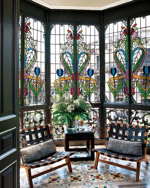a lovely sitting nook with a bay window done with stained glass and black woven chairs plus a dark table with blooms