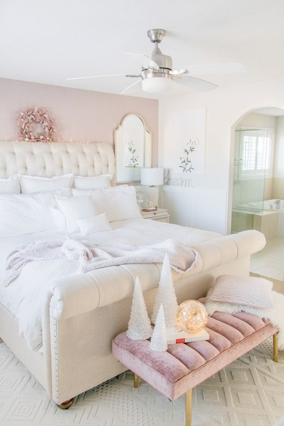 a luxurious bedroom with a pink accent wall, a white upholstered bed and white bedding, a pink velvet bench, a fan and neutral lamps