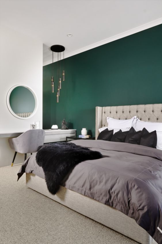 a master bedroom with a green accent wall, a grey upholstered bed, neutral bedding, a vanity with a grey chair and a white dresser