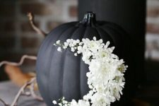 a matte black pumpkin decorated with white flowers as a moon is a beautiful Halloween decoration