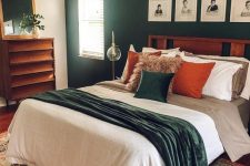 a mid-century modern bedroom with a dark green accent wall, a stained bed and dresser, a gilded chandelier, bright bedding and a mirror in a gilded frame