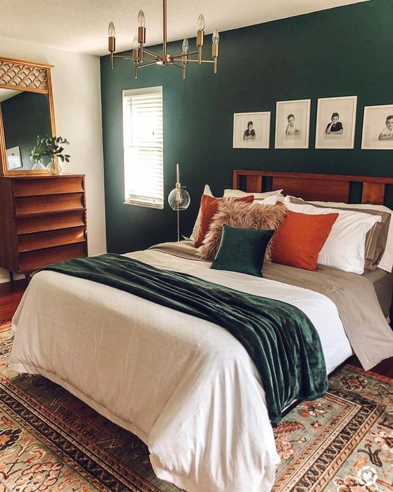 a mid century modern bedroom with a dark green accent wall, a stained bed and dresser, a gilded chandelier, bright bedding and a mirror in a gilded frame
