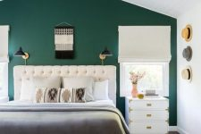 a mid-century modern bedroom with a green accent wall, a creamy upholstered bed, creamy nightstands, a chandelier, some sconces and hats on the wall
