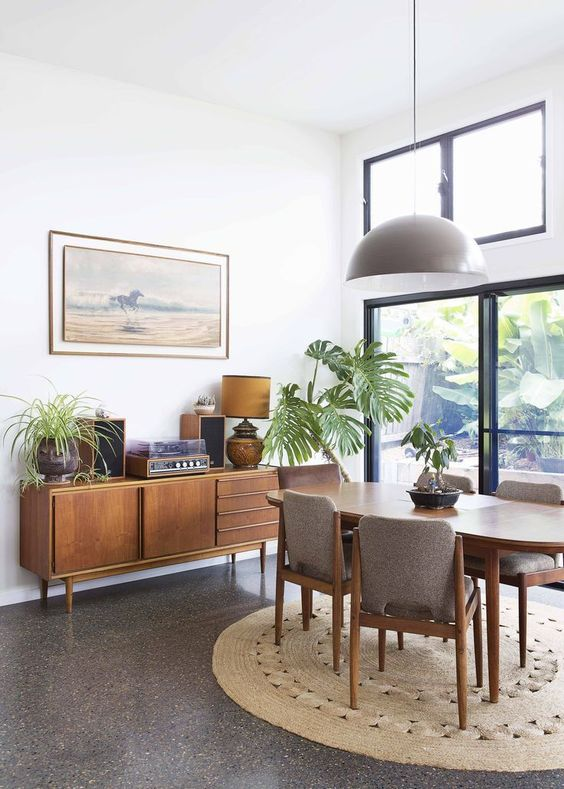 a mid-century modern dining room with lovely stylish furniture, potted plants, an exit to the garden and a clerestory window to illuminate the space