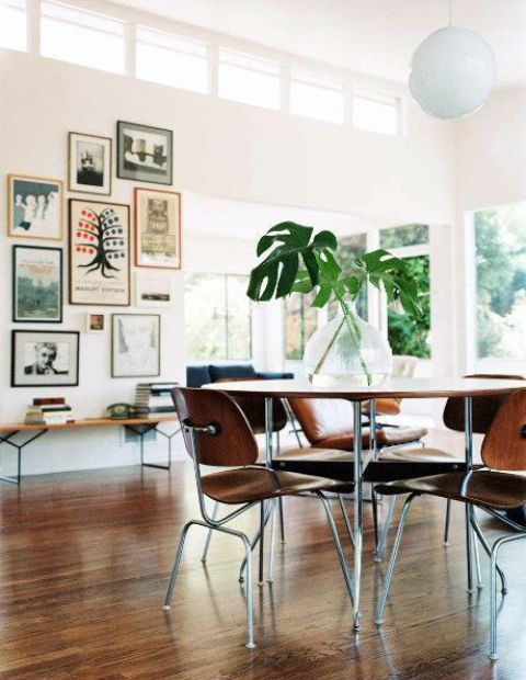 a mid-century modern dining space with a bright gallery wall, a plywood table and chairs, a glazed wall and clerestory windows for more light