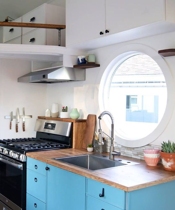 a mid century modern kitchen with white walls, a round window, a white upper cabinet, a blue lower one and butcherblock countertops