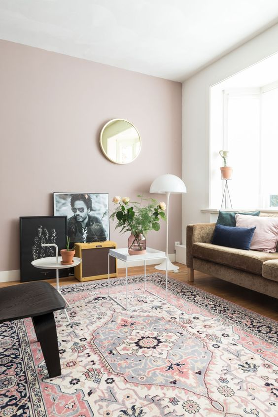 a mid-century modern living room with a brown sofa, pretty colorful pillows, coffee tables, a gallery wall on the floor, a gilded mirror, a black chair