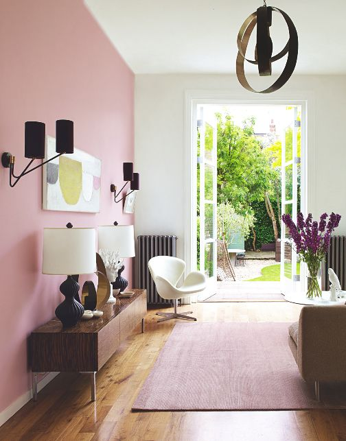 a mid-century modern living room with a pink accent wall, a stained credenza, neutral furniture, a sphere pendant lamp and a bold artwork