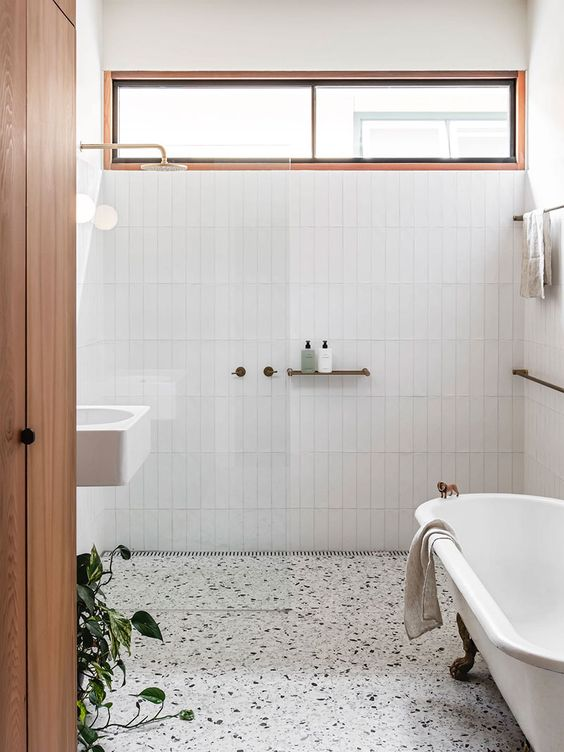 a mid-century modern neutral bathroom with skinny tiles, a terrazzo floor, a clawfoot tub, a clerestory window that brings some light