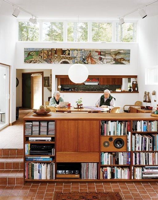 a mid-century modern space with double-height ceilings, with clerestory windows for more natural light, a large bookcase as a space divider