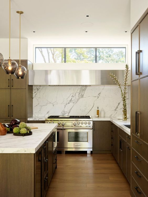 a midern dark wood kitchen with a white marble backsplash and countertops and a clerestory window to make the space lighter and fresher