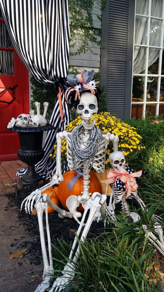 a mini fun skeleton scene with a skeleton girl and a baby dressed up in jewelry and bold fabric bows is a cool idea for Halloween