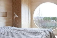 a minimalist bedroom totally clad with plywood, with a large round window, a sleek plywood wardrobe and a bed with neutral textiles