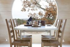 a minimalist dining space with a large porthole window that is a decor feature at once as it provides amazing views and a dining set